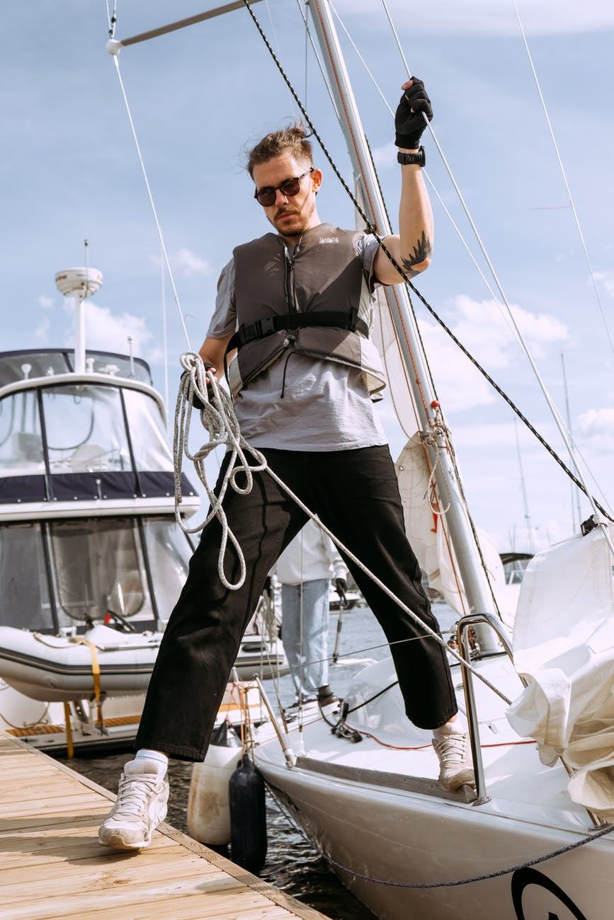 man in black and white jacket and blue denim jeans standing on white boat