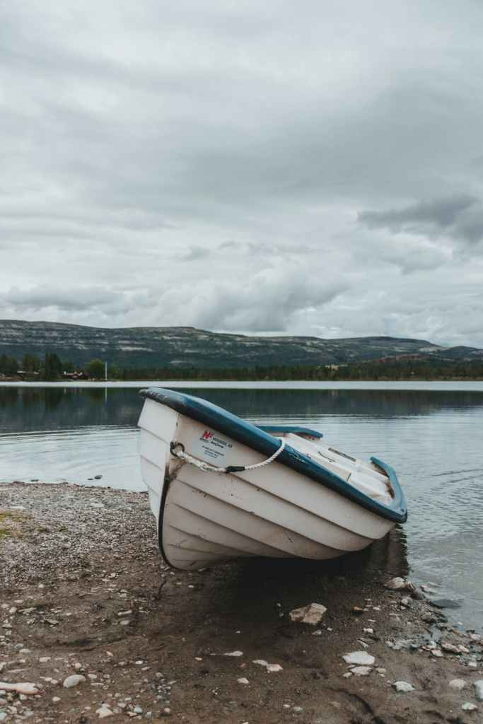 boat on shore against rocky mountains